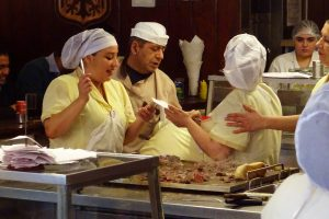 Chefs cooking meat sandwiches at Fuente Alemana, Santiago
