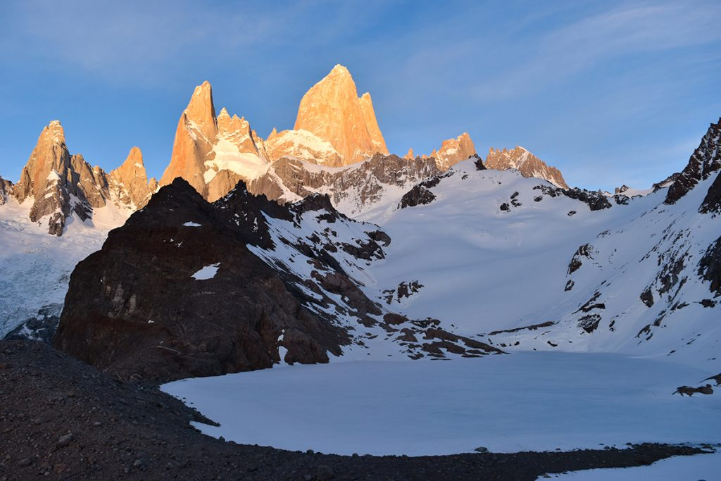 Mount Fitz shimmer orange at sunrise across Laguna de los Tres