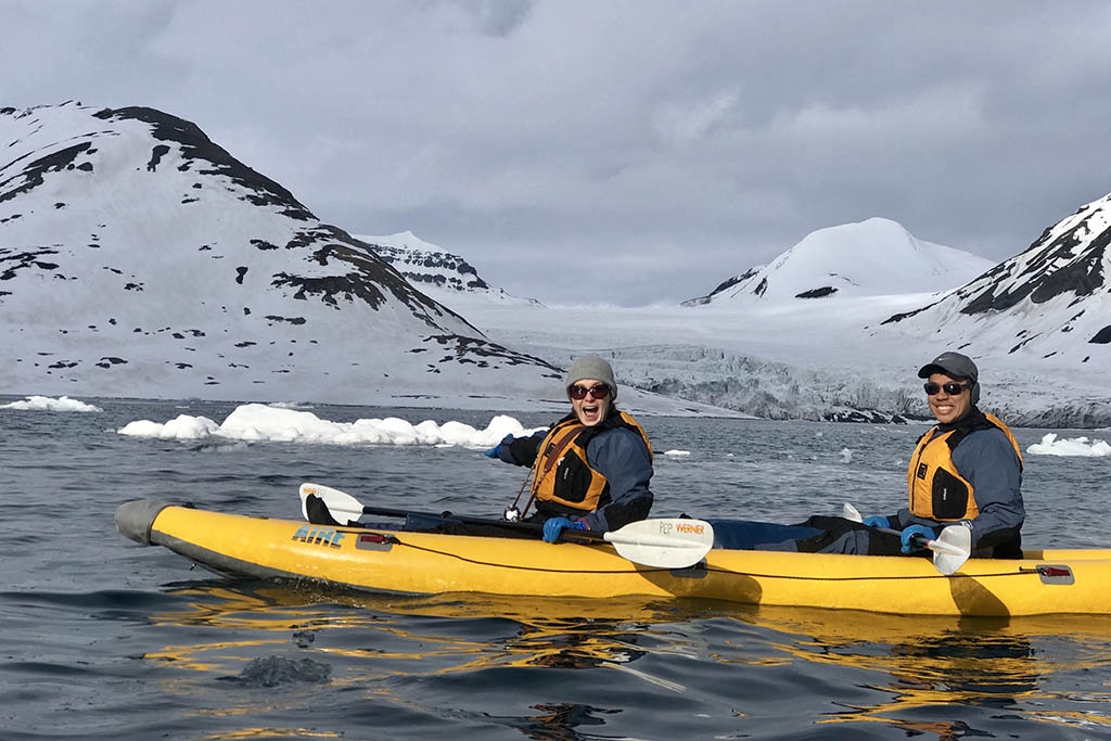 Susie and Jan kayaking in Arctic waters during their travels